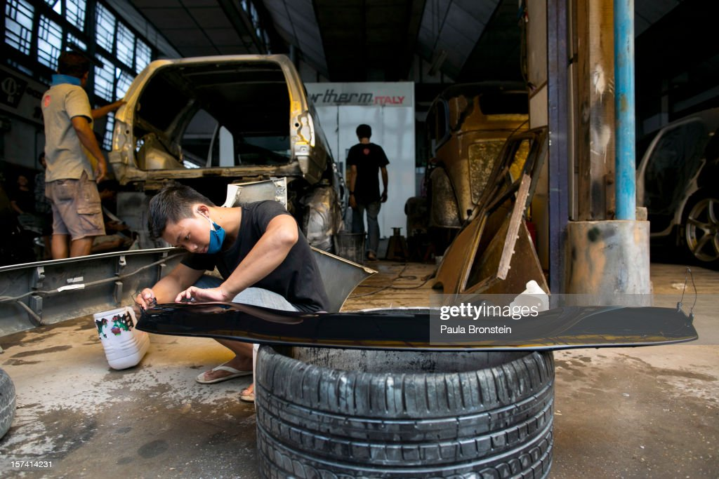 A Burmese worker restores car parts at the Htoo Auto Service workshop November 29, 2012 Yangon, Myanmar. Import restrictions have been eased, resulting in many new cars seen on the streets. Most of the cars are being imported from Japan. In the past importing cars had been strictly limited under the military government until last year. Previously only the ruling elite, politicians and military personnel could obtain permission to import foreign cars.