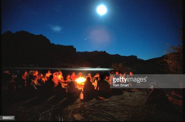 Burn Survivors from the University of Utah Burn Camp form a circle around a campfire to share their stories on the Green River June 17 2000 in...