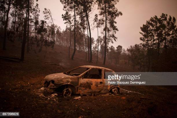 A burned car stand next to a forest after a wildfire took dozens of lives on June 18 2017 near Castanheira de Pera in Leiria district Portugal On...