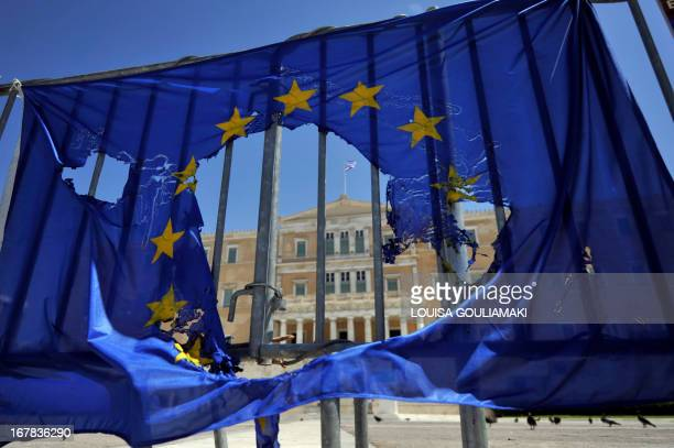 A burned EU flag hangs on the barriers protecting the Greek parliament in Athens on May 1 2013 Greece's two main unions called a general strike...