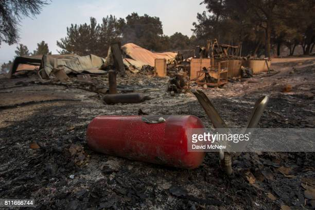 A burned fire extinguisher is seen next to structures at Rancho Alegre Boy Scouts of America outdoor school that were destroyed by the Whittier Fire...