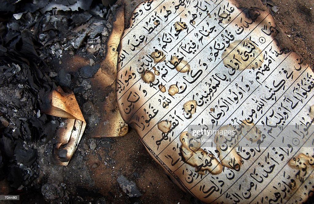 A burned Koran lies outside of the home of murdered Muslims who had been killed the day before March 2 2002 in Ahmadabad India Troops arrived in...