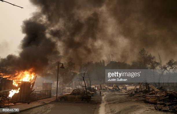 Burned out cars sit next to a building on fire in a fire ravaged neighborhood on October 9 2017 in Santa Rosa California Ten people have died in...