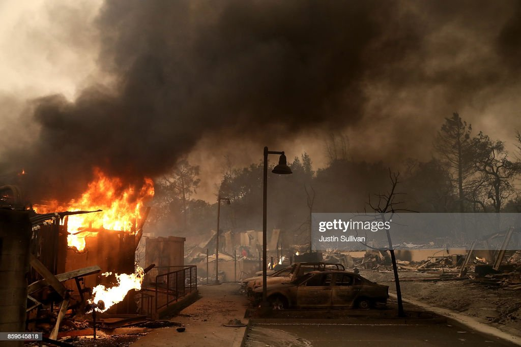 Burned out cars sit next to a building on fire in a fire ravaged neighborhood on October 9, 2017 in Santa Rosa, California. Ten people have died in wildfires that have burned tens of thousands of acres and destroyed over 1,500 homes and businesses in several Northen California counties.