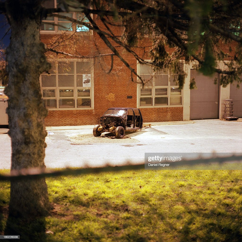 CONTENT] A burned out destroyed automobile is laid in front of a building. A car is totally destroyed parked in front of a brick building. The shot peers over the fence at the scene.
