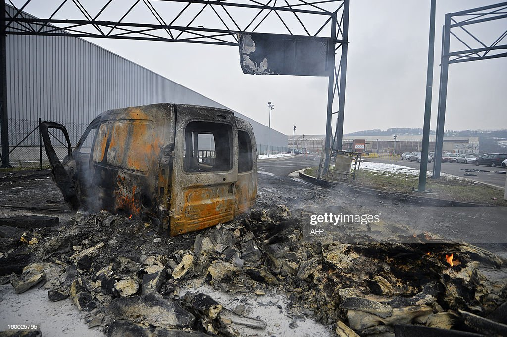 A burned out vehicle is pictured on the parking lot of the Centre Acier in front of the headquarters of ArcelorMittal on January 25, 2013 in Flemalle. Steelmaker ArcelorMittal announced yesterday the closure of the cold lines in Liege, 1300 jobs are threatened. Protesting workers gathered yesterday in front of the headquarters.