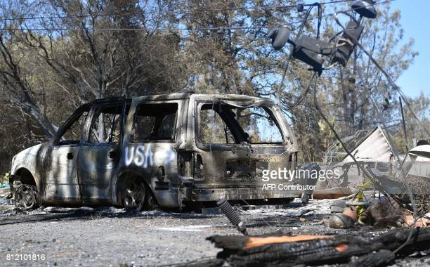 A burned out vehicle is seen near some felled power lines at a residential property after the Wall fire tore through the area and burned dozens of...