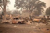 Burned out vehicles are surrounded by smoldering rubble while firefighters continue to battle the Valley fire in Middletown California on September...
