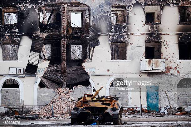 A burned Ukrainian military vehicle is seen in front of a destroyed building on February 7 2015 in Uglegorsk Ukraine According to ProRussian rebels...