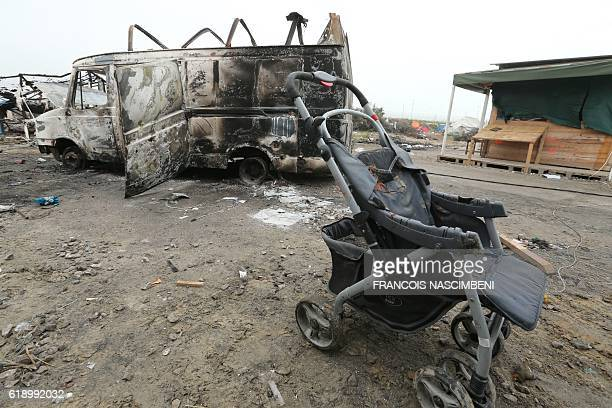 A burned vehicle and pushchair are seen in the 'Jungle' migrant camp in Calais northern France on October 29 during a massive operation to clear the...