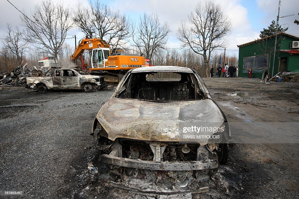 A burned-out car sits sits near a still smouldering truck on the site of a gold mining company in the forest of Skouries, some 620kms north of Athens, on February 17, 2013. Dozens of hooded men firebombed the premises of a Greek subsidiary of a Canadian gold mining company today, injuring a guard and damaging containers, cars and trucks. The site has faced opposition from citizens' groups who fear the project will cause irreversible harm to the local environment. They have been trying to halt the project since 2011, when the Greek government allowed Hellenic Gold, a subsidiary of Canadian company Eldorado Gold, to dig in the region. AFP PHOTO /Sakis Mitrolidis