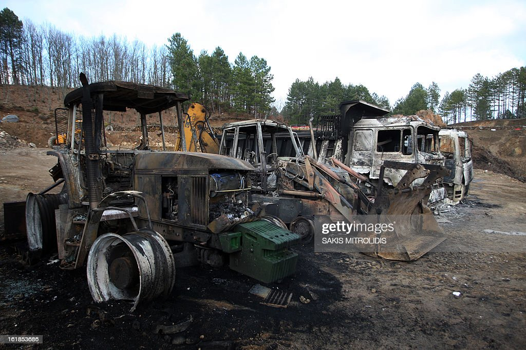 Burned-out tractors and trucks are pictured on the Hellenic Gold site in the forest of Skouries, some 620kms north of Athens, on February 17, 2013. Dozens of hooded men firebombed the premises of a Greek subsidiary of a Canadian gold mining company today, injuring a guard and damaging containers, cars and trucks. The site has faced opposition from citizens' groups who fear the project will cause irreversible harm to the local environment. They have been trying to halt the project since 2011, when the Greek government allowed Hellenic Gold, a subsidiary of Canadian company Eldorado Gold, to dig in the region. AFP PHOTO /Sakis Mitrolidis