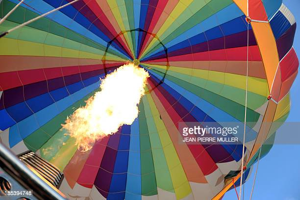 Burners inflate a hot air balloon before overflying the famous vineyards near the village of Saint Emilion on October 19 2013 AFP PHOTO/ JEAN PIERRE...