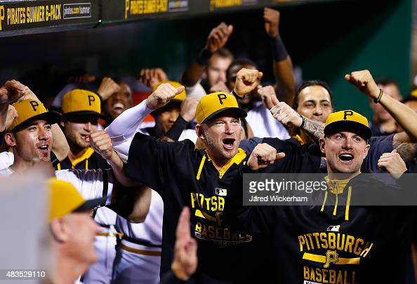 J Burnett and Jordy Mercer of the Pittsburgh Pirates reacts in the dugout with teammates following a three run home run in the 7th inning by Jung Ho...