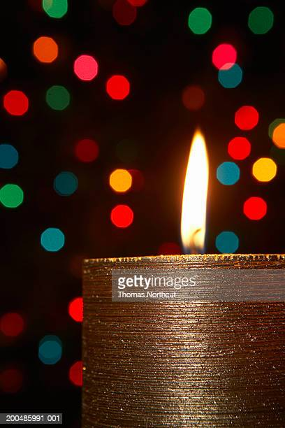 Burning candle with Christmas lights in background