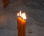 burning candles on a candle stand in the church