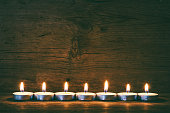 burning candles on the background of old barn boards, tinted photo