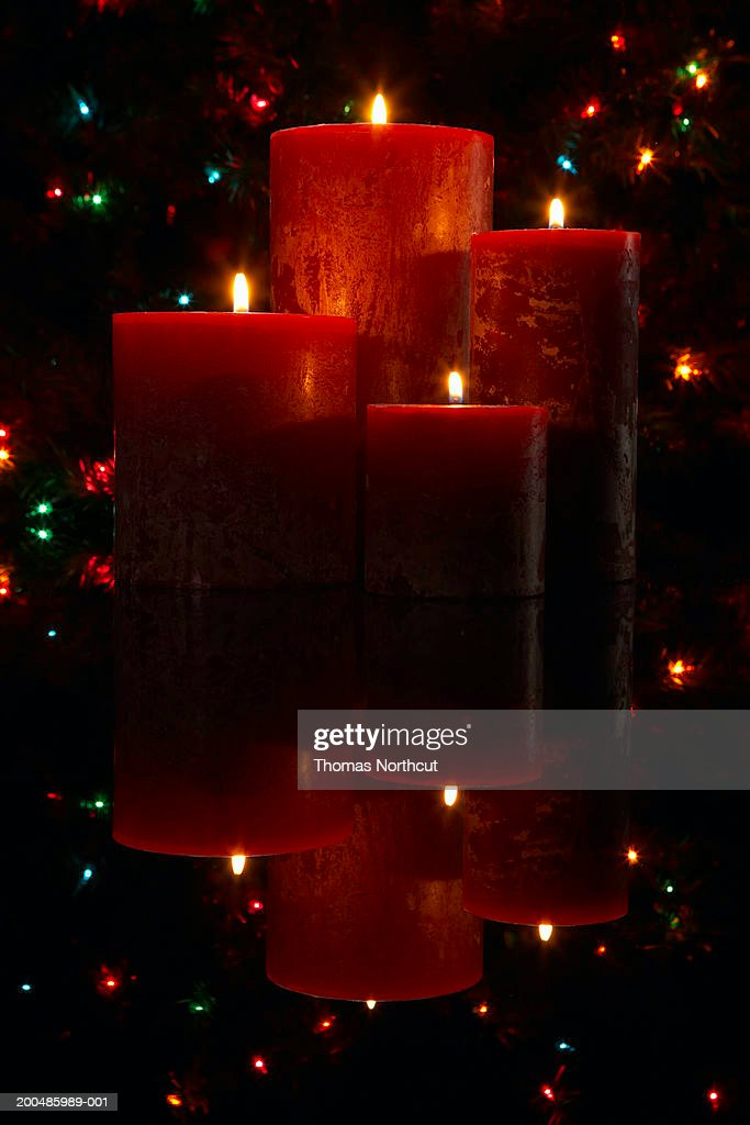 Burning candles with Christmas lights in background : Stock Photo