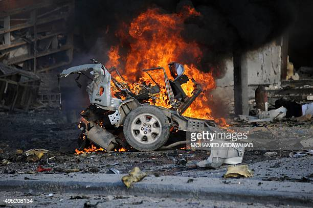 A burning car is seen on November 1 2015 near the damaged Sahafi hotel in Mogadishu after an explosion At least 12 people were killed in the Somali...