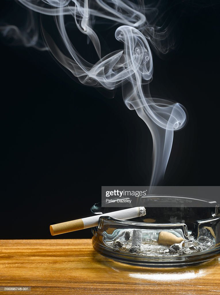 Burning cigarette in ashtray on table