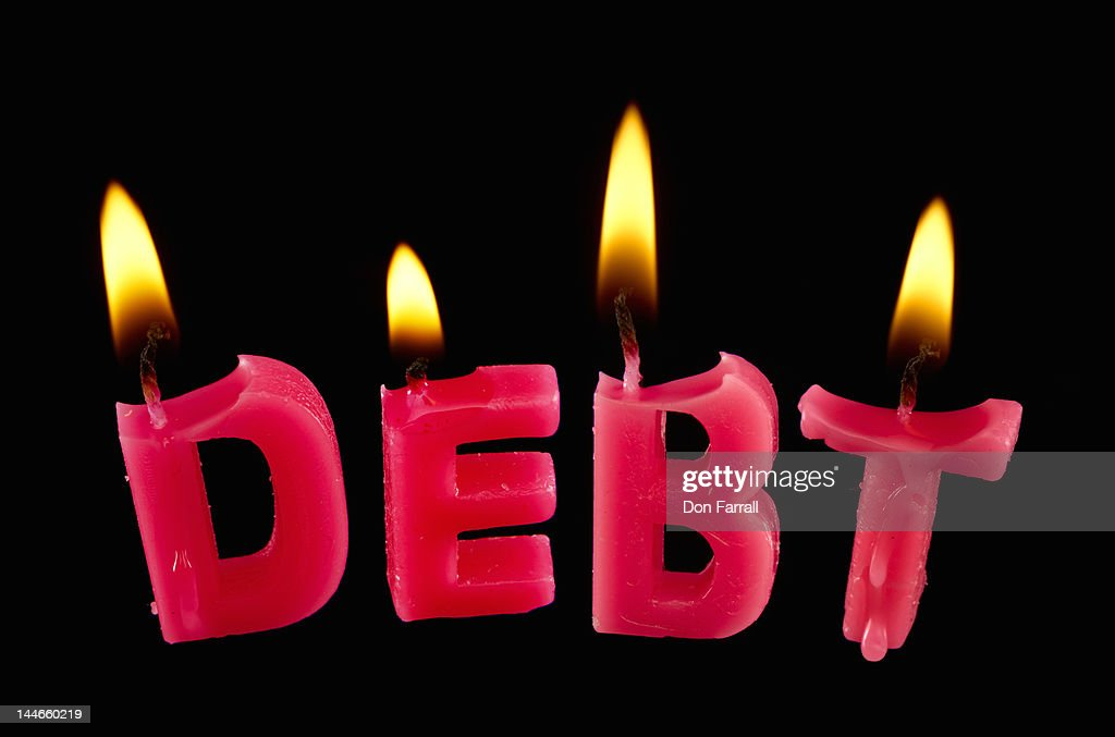 Burning 'debt' candles : Stock Photo