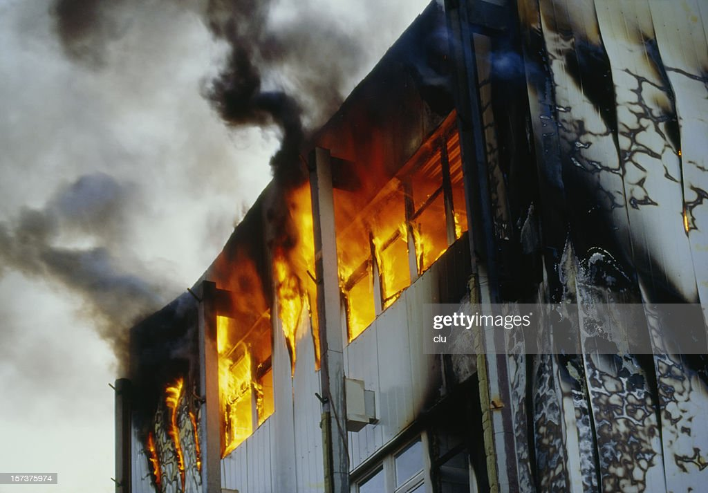 Burning house upper floor and and ascending black smoke : Stock Photo