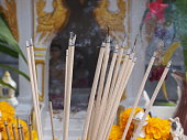 burning incense sticks on blurred background of spirit house with waving smoking