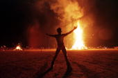 A 'Burning Man' participant holds up his arms as the wooden man effigy is burned at the conclusion of the weeklong 'Burning Man Festival' 06...