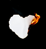 heart shape paper burning on black background