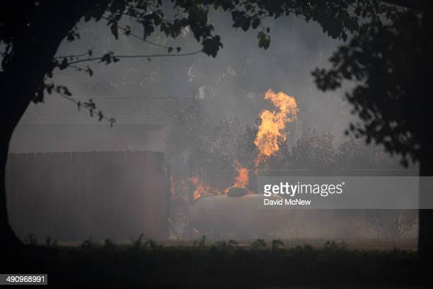 A burning propane tank vents near a house at the Cocos fire on May 15 2014 in San Marcos California Fire agencies throughout the state are scrambling...
