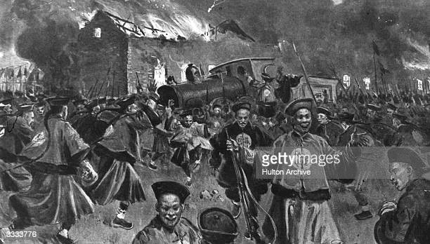 A burning station and derailed train on the Manchurian railway with Chinese nationalists celebrating their action during the Boxer Rebellion Original...