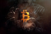 Burning symbol of bitcoin with man in the background. Conception of risk management in money trading at currency market