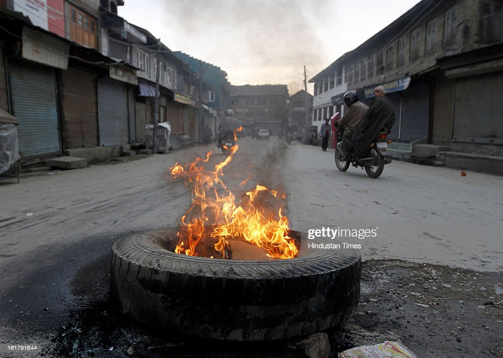 A burning tire stands on a road during a strike called by separatist organizations in protest for hanging of Afzal Guru on February 16, 2013 in Srinagar, India.The week-long curfew restrictions have been removed today, though security forces would continue to monitor the situation as a separatist group has called for a strike for another two days.