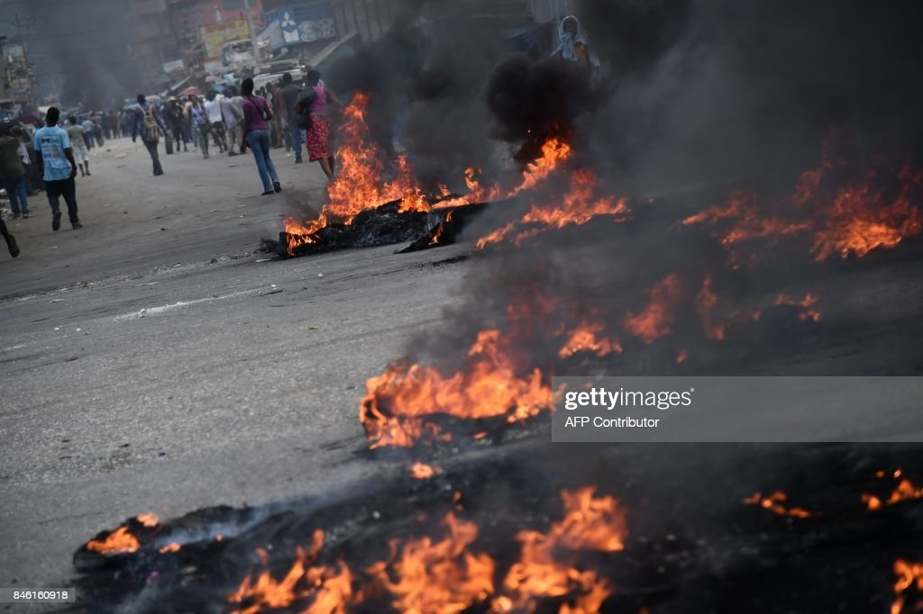 Burning tires are placed by protesters on a main road in the centre of the Haitian capital Port-au-Prince, on September 12, 2017. Demonstrators took to the streets to protest against the government and the new budget for 2018, throwing stones at the police, setting tires on fire and blocking some streets. /