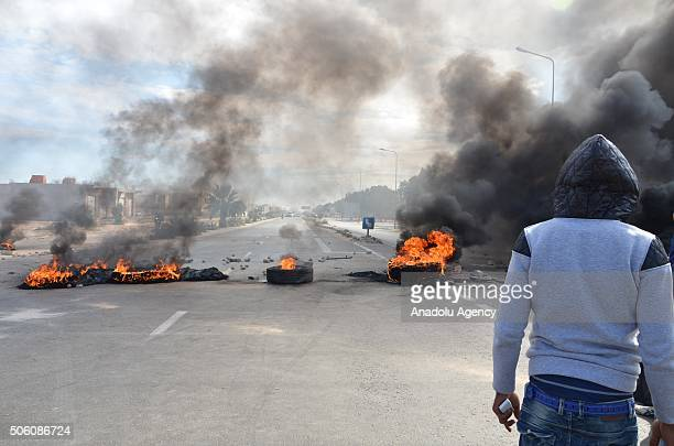 Burning tires are seen at a blocked road during a protest staged by unemployed young citizens against unemployment and poverty in Tataouine Tunisia...