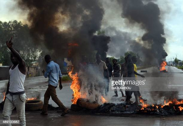 Burning tires form a barrier across a main road as people protest on September 19 2015 in Ouagadougou Burkina Faso's capital The protest comes...