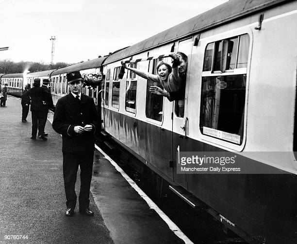 Burnley fans cheer as they leave on the British Rail special from Burnley Central Station