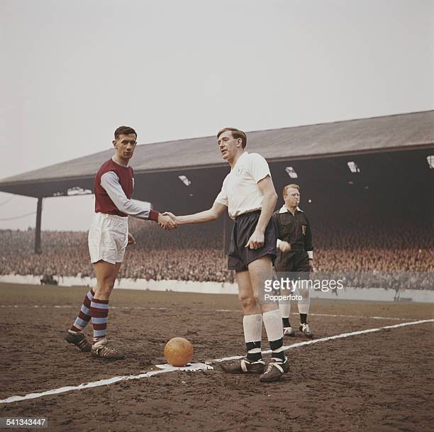 Burnley FC football captain Jimmy Adamson shakes hands with Danny Blanchflower of Tottenham Hotspur before kick off at a league game at Burnley's...