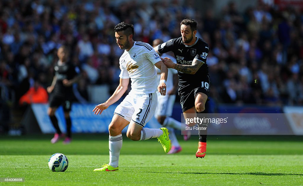 Burnley forward Danny Ings (r) challenges Swansea player Jordi Amat during the Barclays Premier League match between Swansea City and Burnley at Liberty Stadium on August 23, 2014 in Swansea, Wales.