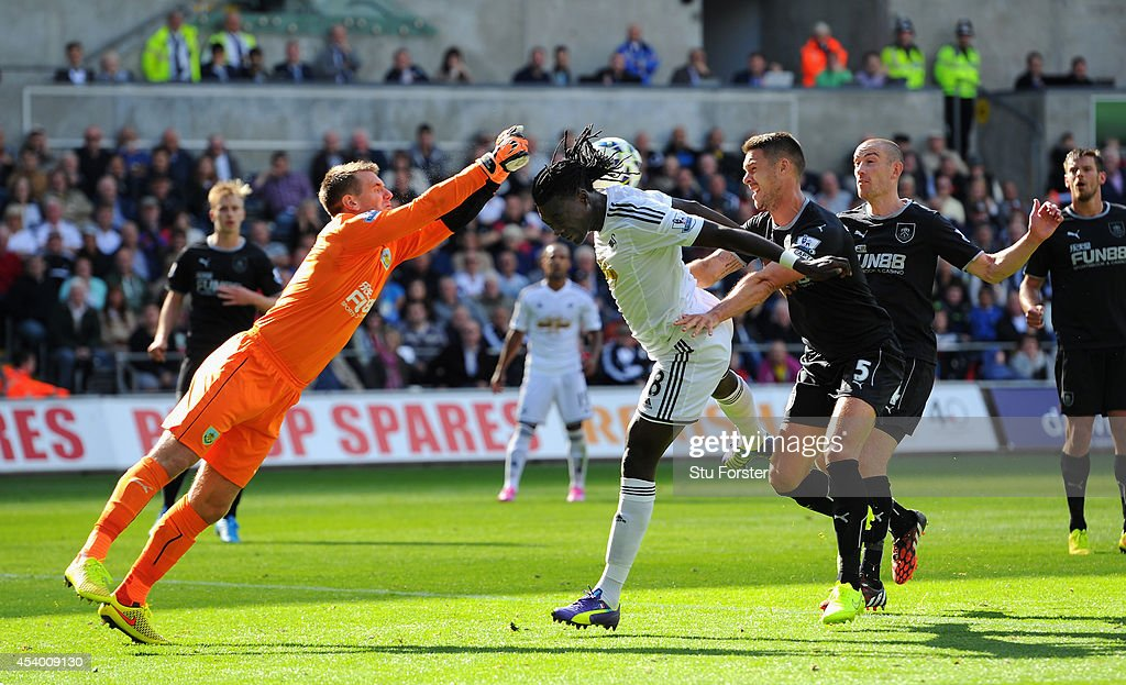 Burnley goalkeeper Tom Heaton saves from the head of Swansea forward <a gi-track='captionPersonalityLinkClicked' href=/galleries/search?phrase=Bafetimbi+Gomis&family=editorial&specificpeople=686005 ng-click='$event.stopPropagation()'>Bafetimbi Gomis</a> during the Barclays Premier League match between Swansea City and Burnley at Liberty Stadium on August 23, 2014 in Swansea, Wales.