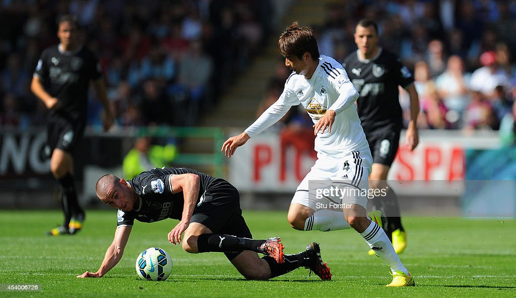 Burnley player David Jones (l) is challenged by Swansea player Ki Sung-Yueng (r) during the Barclays Premier League match between Swansea City and Burnley at Liberty Stadium on August 23, 2014 in Swansea, Wales.