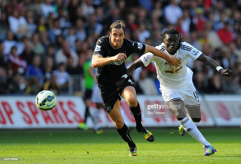 Burnley player Michael Duff (l) challenges Swansea forward <a gi-track='captionPersonalityLinkClicked' href=/galleries/search?phrase=Bafetimbi+Gomis&family=editorial&specificpeople=686005 ng-click='$event.stopPropagation()'>Bafetimbi Gomis</a> during the Barclays Premier League match between Swansea City and Burnley at Liberty Stadium on August 23, 2014 in Swansea, Wales.