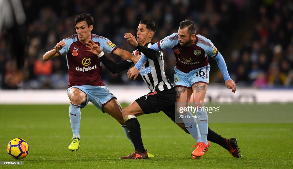 Burnley players Jack Cork (l) and Steven Defour combine to thwart Ayoze Perez of Newcastle during the Premier League match between Burnley and Newcastle United at Turf Moor on October 30, 2017 in Burnley, England.