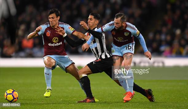 Burnley players Jack Cork and Steven Defour combine to thwart Ayoze Perez of Newcastle during the Premier League match between Burnley and Newcastle...