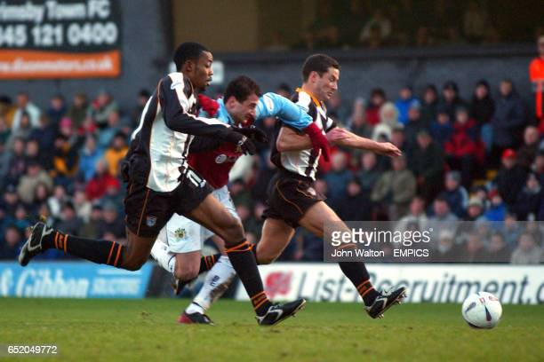 Burnley's Dimi Papadopoulos is held back by a combination of Grimsby Town's Simon Ford and John McDermott
