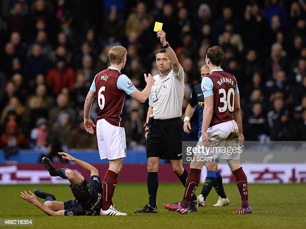 Burnley's English defender Ben Mee is shown a yellow card by referee Andre Marriner during the English Premier League football match between Burnley...