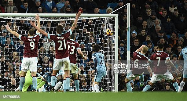 Burnley's English defender Ben Mee scores his team's first goal during the English Premier League football match between Manchester City and Burnley...
