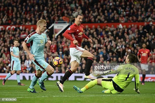 Burnley's English goalkeeper Tom Heaton saves a shot from Manchester United's Swedish striker Zlatan Ibrahimovic during the English Premier League...