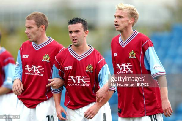 Burnley's Ian Moore Paul Weller and Luke Chadwick form a defensive wall