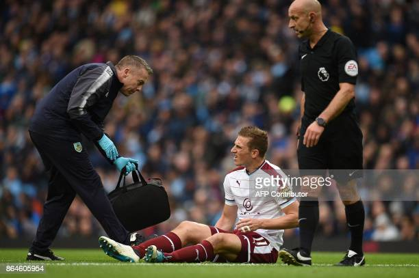 Burnley's New Zealand striker Chris Wood receives medical treatment atfter clashing with Manchester City's Brazilian goalkeeper Ederson during the...
